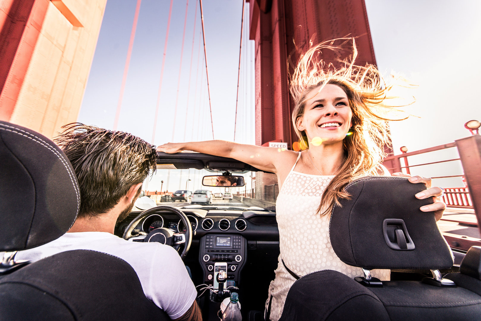 Couple enjoying a ride on the Golden Gate bridge in a red convertible.